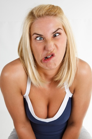 bad color: A young blond woman with a freaky grimace - isolated on white