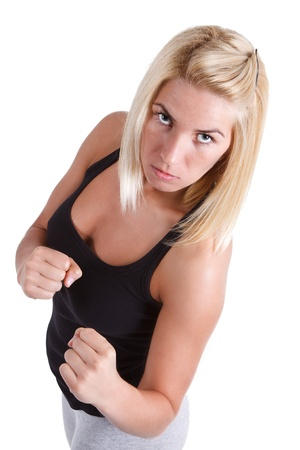 Young and attractive blond sportswoman in a sexy black top boxing, looking into the camera - isolated on white Stock Photo