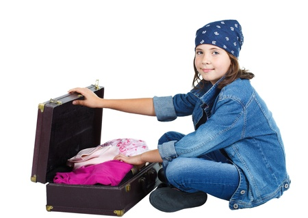 Cute 9-year-old smiling girl in jeans and scarf on head, sitting on floor, opening a suitcase full of clothes - isolated on white