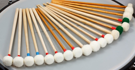 Marimba mallets with white heads resting in a quarter circle