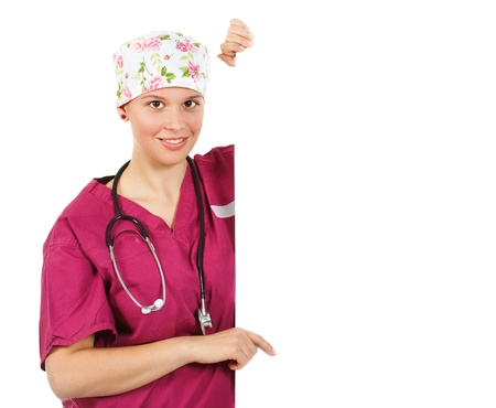 An attractive young female doctor in purple uniform, cap, stethoscope round her neck, pointing on a white, blank board, smiling into camera - isolated on white photo