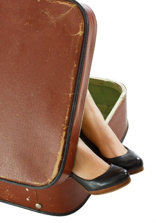 Close-up of female feet with black shoes in a retro suitcase - isolated on white