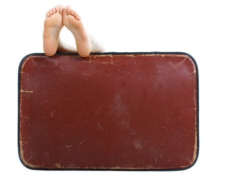 Old brown suitcase female feet resting on top - isolated on white photo