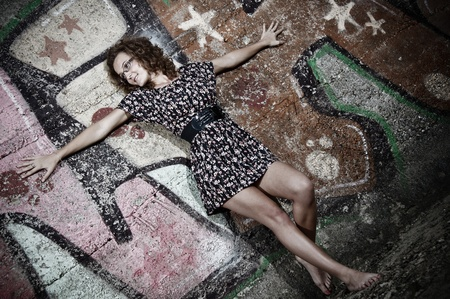 Portrait of girl with curly hair, glasses, wearing short dress, leaning against wall with graffiti outdoors
