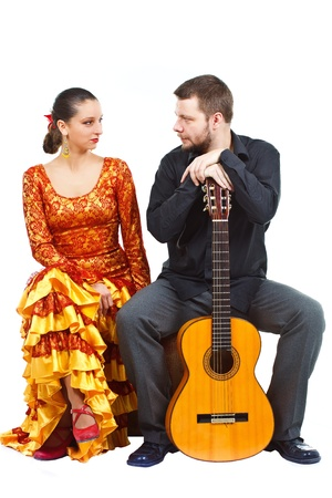 Portrait of a woman flamenco dancer and a man guitarist sitting on an old suitcase, man holding a guitar, they are smiling at each other - isolated on white photo