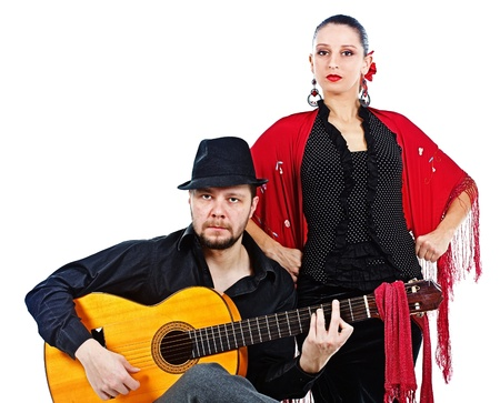 Portrait of a woman flamenco dancer in black and red clothes, standing behind a man guitarist wearing black hat, playing his guitar, both looking into camera - isolated on white