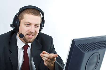 Portrait of young businessman with headset showing and smiling at a monitor - isolated on white Stock Photo
