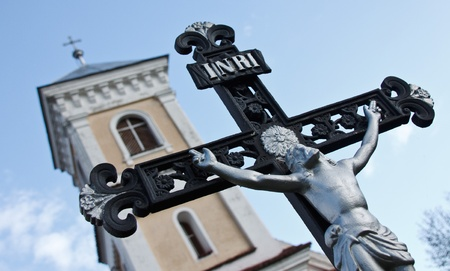 Close-up of a crucifixwith Christ with the tower of a Roman catholic church in the background photo