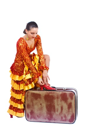 Portrait of a female flamenco dancer in orange and yellow dress, putting on her red dancing shoe on an old brown suitcase - isolated on white Stock Photo