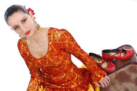 Portrait of a female flamenco dancer in orange and yellow dress, sitting on an old brown suitcase in studio, her red shoes resting on the suitcase next to her - isolated on white