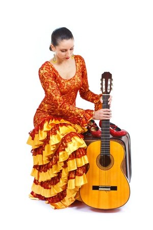 Portrait of a female flamenco dancer in orange and yellow dress, sitting on an old brown suitcase, holding a guitar, looking down at it - isolated on white photo