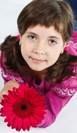 Close-up of a cute 9-year-old girl looking up into camera, holding a pink flower