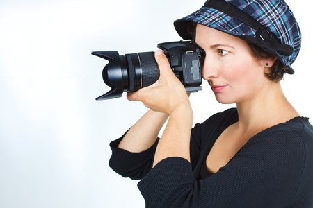 Portrait of a young woman photographer with a checked hat, wearing black top - isolated on white
