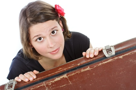 Portrait of an attractive young woman looking into camera from behind an old brown suitcase - isolated on white photo