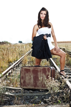 An attractive young woman with long brown hair, wearing white mini dress, standing on railroad with an old suitcase photo