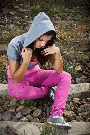 down sitting: A girl in pink and grey clothes looking down, sitting on the ground outdoors