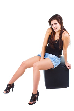 Portrait of a beautiful young woman with long brown hair, in mini skirt, black top, black high-heel shoes, sitting on black stool, smiling into camera - isolated on white photo