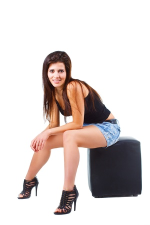 Portrait of a beautiful young woman with long brown hair, in mini skirt, black top, black high-heel shoes, sitting on black stool, smiling into camera - isolated on white Stock Photo - 11961019