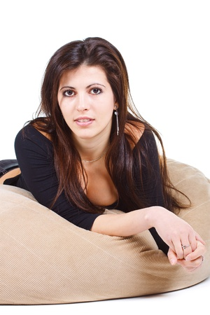 Portrait of a beautiful young woman with long brown hair, resting on a bolster, looking into camera - isolated on white photo