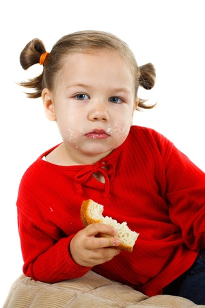 A beautiful little girl with blue eyes, wearing red jumper, looking into the camera with smeary face, wearing red top, holding a piece of bread in her hand - isolated on white  photo