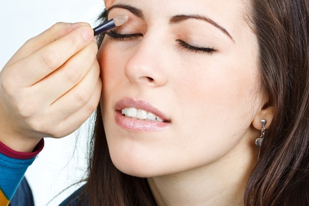 else: Portrait of a beautiful young woman with brown hair, somebody else is doing her make-up, painting eyelids, eyes closed - isolated on white Stock Photo