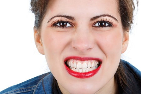 Close-up of a beautiful young womans face, showing her teeth, wearing red lipgloss, big brown eyes, looking into camera - isolated on white