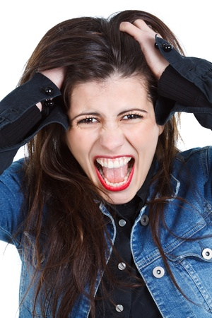 Beautiful young woman with long brown hair screaming with anger, hands in her hair, looking into camera - isolated on white photo