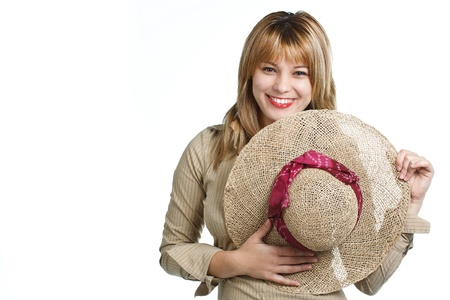 Portrait of a smiling young woman holding a straw hat, looking into camera - isolated on white