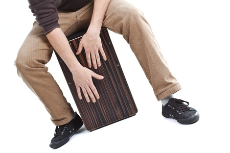 Close-up of a cajon, mans legs and hands are shawn as hes playing the instrument - isolated on white