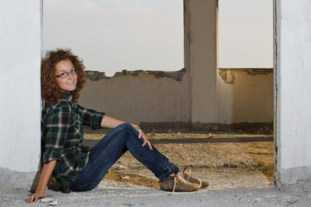 Portrait of a teenage girl with curly hair, glasses, wearing shirt and jeans, sitting on ground outdoors