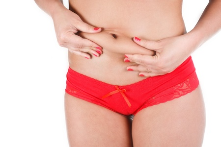 Close-up of a womans belly, wearing red underpants, grabbing her fat on her belly, nails are red - isolated on white Stock Photo