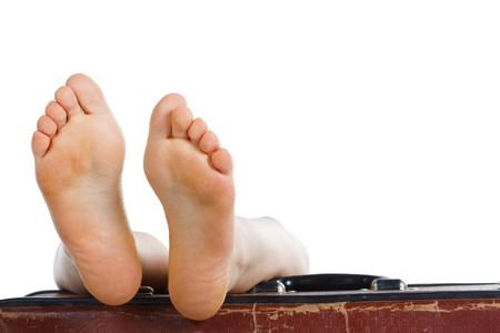 Close-up der weiblichen Füße, zwei Sohlen, ruht auf der Oberseite des alten braunen Koffer - isoliert auf weiß