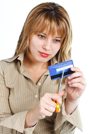 Portrait of a young beautiful woman with blond hair cutting her credit card or bank card with yellow scissors - isolated on white photo