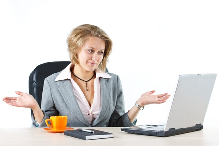 freaked: Portrait of a young businesswoman sitting at desk, looking at laptop, hands in do not know gesture - isolated on white