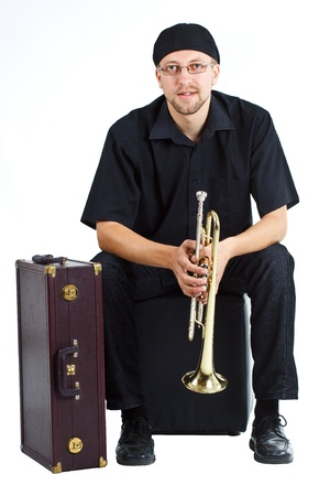 Young man wearing cap and glasses, sitting with a suitcase, holding a trumpet - isolated on white Stock Photo