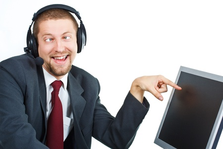 Portrait of young businessman with funny grimace with headset showing and smiling at a monitor - isolated on white photo