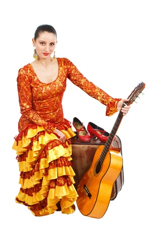 Portrait of a female flamenco dancer in orange and yellow dress, sitting on an old brown suitcase, holding a guitar, smiling into camera - isolated on white