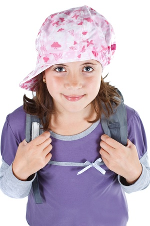 Portrait of a cute 9-year-old girl wearing a cap, holding her rucksack with her hands, smiling into camera - isolated on white Stock Photo