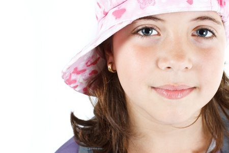 Close-up of a cute 9-year-old girl wearing a cap, smiling into camera - isolated on white Stock Photo