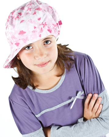 Portrait of a cute 9-year-old girl wearing a cap, with crossed arms, smiling into camera - isolated on white