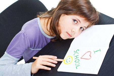 Portrait of a cute 9-year-old schoolgirl, resting her head on the desk, on a sheet of paper with