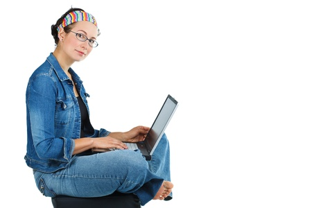 Portrait of a young attractive woman with glasses, wearing a headband, jeans, sitting crossed legs on a stool with a laptop in her lap, smiling at camera - isolated on white Stock Photo