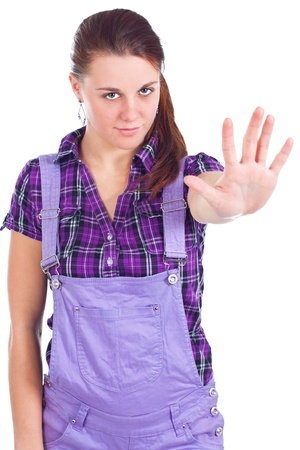 Portrait of young attractive woman with long red hair, with pony tail, wearing purple checked shirt, showing stop sign with her hand - isolated on white Stock Photo