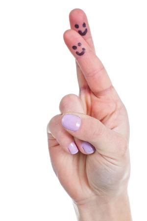 mani incrociate: Close-up di una mano femminile con le dita incrociate, facce divertenti tratti su dita - isolato su bianco Archivio Fotografico