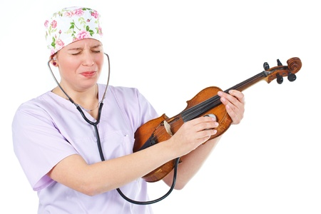 violin making: An attractive young female doctor wearing a light purple uniform and cap, checking a violin with stethoscope, making funny grimace - isolated on white Stock Photo