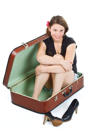 A beautiful young woman in shorts and top, barefoot, sitting in a suitcase, shoes on the floor, girl looking into camera - isolated on white photo