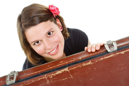 Portrait of an attractive young woman smiling into camera from behind an old brown suitcase - isolated on white photo