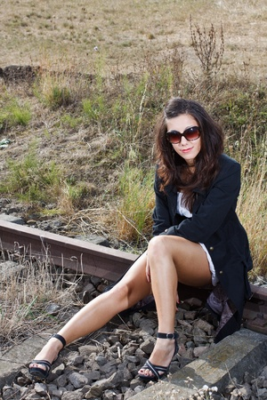 A beautiful young woman with long brown hair wearing a black jacket, black sandals and sunglasses, sitting on the rail, looking photo