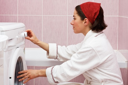 Portrait of attractive young woman in robe, starting her washing machine in her bathroom
