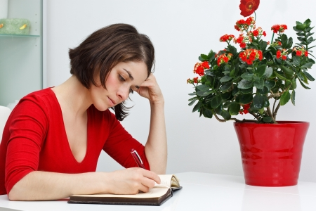 Portrait of a beautiful young woman wearing red top, sitting at home at her desk, looking down and writing, green and red flowers in red pot photo